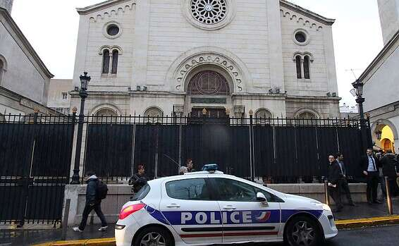 A police car is parked in front of a synagogue in France