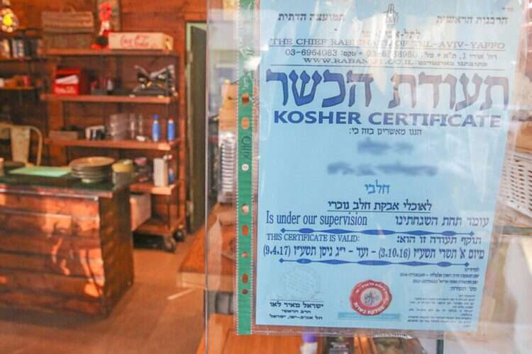 A kashrut certificate is displayed in the front window of a Tel Aviv eatery